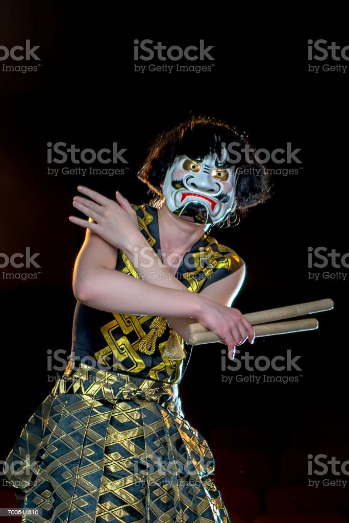 drummer girl in white demon mask stands with her hands cross holds the drumsticks, studio shot on a dark background. stock photo