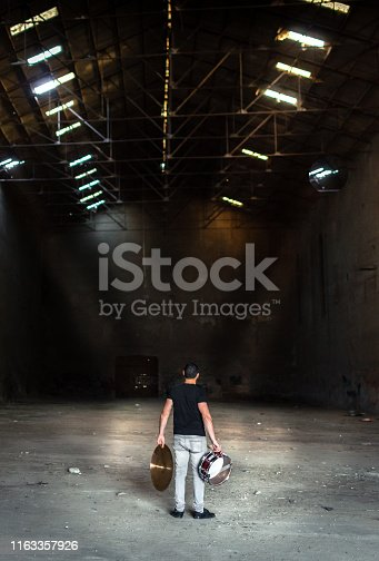 Drummer man holding drum and cymbal in dark abandoned warehouse full of debris. Preparing music party or rave in abandoned place with beautiful light..