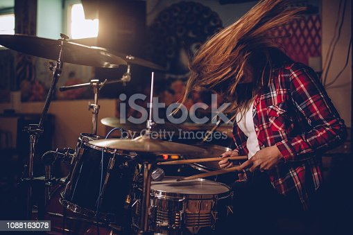 Female drummer playing in the club