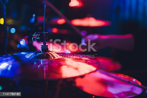 Drummer playing drum set at concert on stage. Music show. Bright scene lighting in club,drum sticks in hands