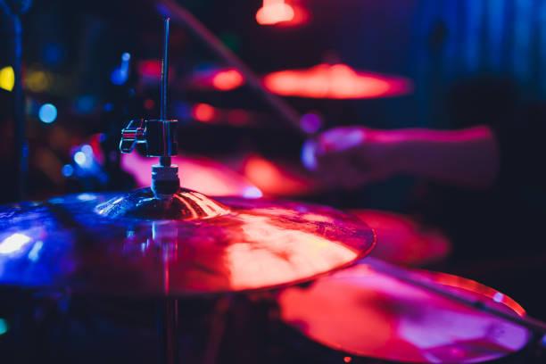 Drummer spielt Schlagzeug auf der Bühne Musikshow. Helle Szenenbeleuchtung im Club, Trommelstifte in Händen. – Foto
