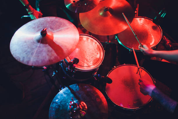 Drummer playing drum set at concert on stage. Music show. Bright scene lighting in club,drum sticks in hands. Drummer playing drum set at concert on stage. Music show. Bright scene lighting in club,drum sticks in hands drummer stock pictures, royalty-free photos & images