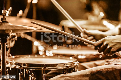 view and shot from backstage: drummer playing hi hat and snare drum