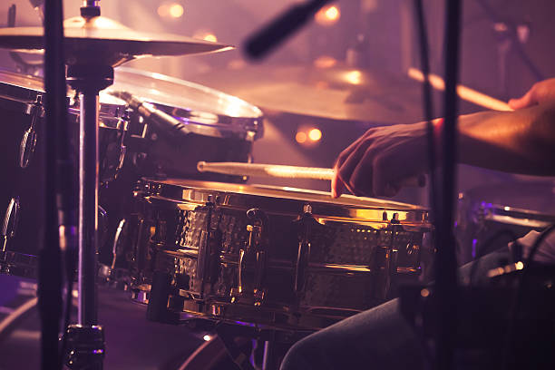 Drummer plays on drum set, vintage Vintage toned live music background, drummer plays with drumsticks on rock drum set. Closeup photo with soft selective focus drummer stock pictures, royalty-free photos & images