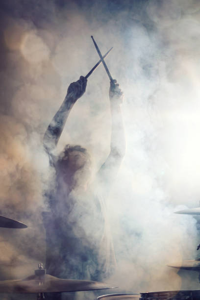 Drummer posing surrounded by fog Drummer in epic posture with crossed sticks surrounded by dense fog. drummer stock pictures, royalty-free photos & images