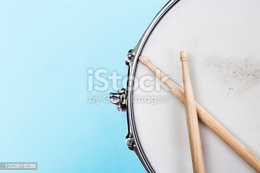 Fragment of a Snare drum and drumsticks on light blue background with copy space for text. Music festival and study and school advertising concept
