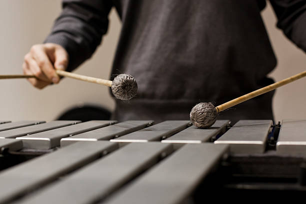 Drumsticks hits the vibraphone Drumsticks hits the vibraphone closeup in dark colors percussion instrument stock pictures, royalty-free photos & images