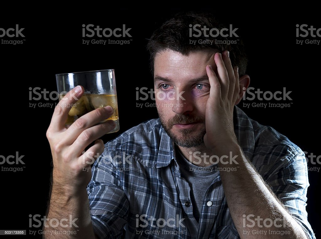 drunk alcoholic man looking at whiskey glass in alcoholism concept stock photo
