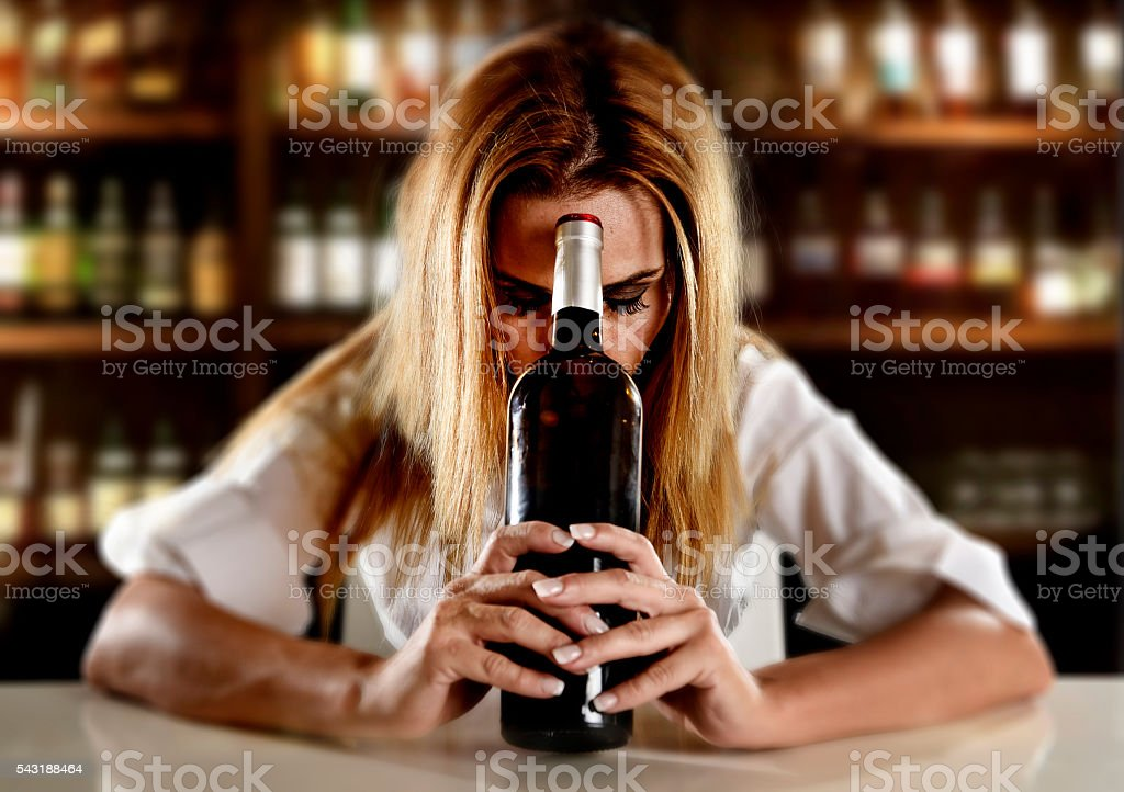 drunk alcoholic woman alone depressed with wine bottle in bar stock photo