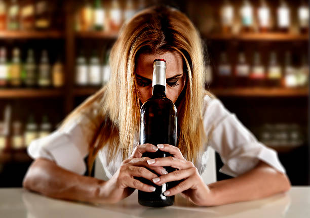 drunk alcoholic woman alone depressed with wine bottle in bar – Foto