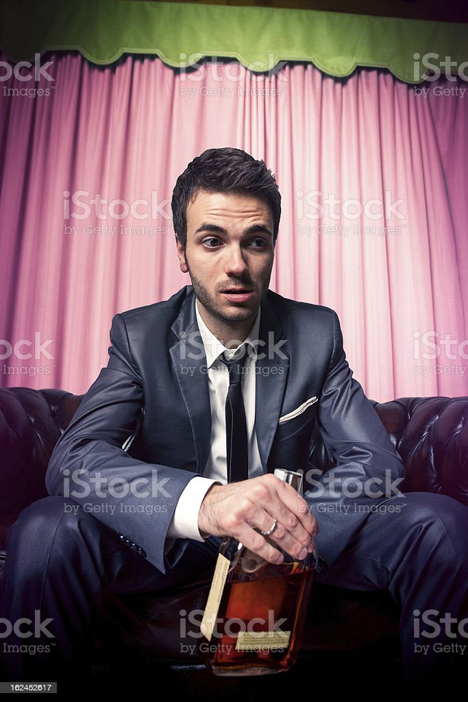 Drunk businessman with a bottle of strong alcohol royalty-free stock photo