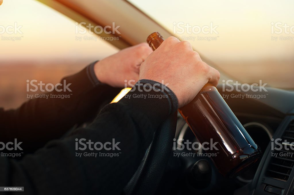 Drunk driver with beer bottle, closeup stock photo
