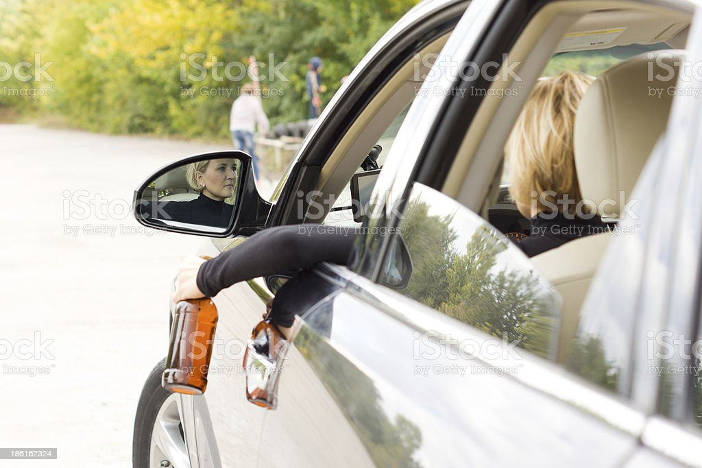 Drunk female dangling a bottle outside the car royalty-free stock photo