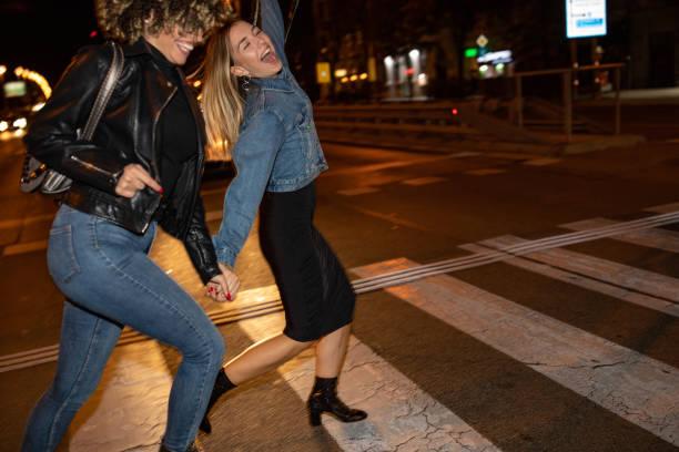 Drunk female friends crossing the street stock photo