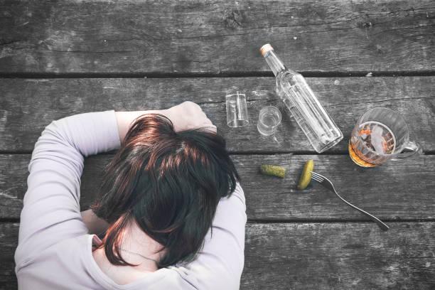 Jeune fille ivre dormant à l'ancienne table en bois après la fête. Bouteille de tasse de vodka et de cornichons, de coups de feu et de bière. Alcoolisme féminin. Gueule de bois. Dépendance à l'alcool. Mauvaise habitude. - Photo