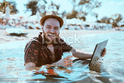 Bearded Guy With Straw Hat Watching Movie On Laptop In The Water
