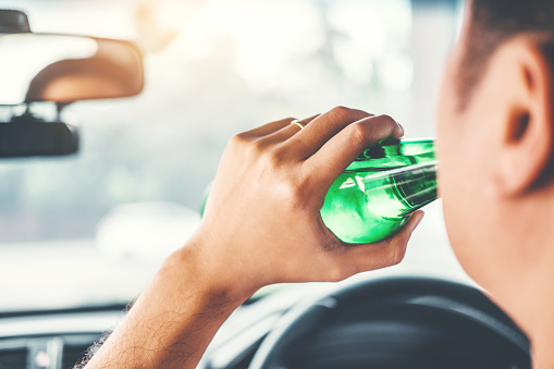 istock Drunk man driving a car on the road holding bottle beer Dangerous drunk driving concept 1089938652