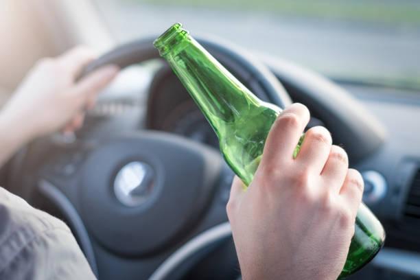 Homem bêbado dirigindo seu carro e beber - foto de acervo