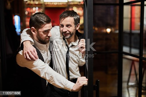 Waist up portrait of waiter carrying drunk man out of bar at night, copy space