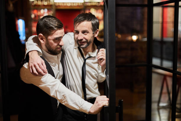 Drunk Man Leaving Pub Waist up portrait of waiter carrying drunk man out of bar at night, copy space drunk stock pictures, royalty-free photos & images