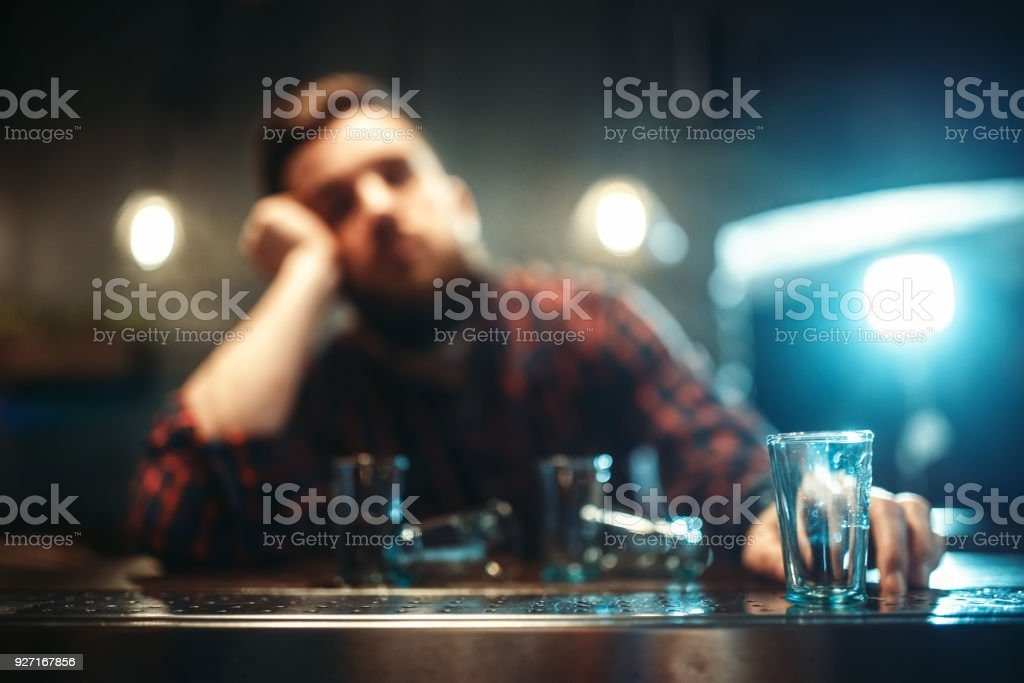 Drunk man sleeps at bar counter, alcohol addiction stock photo