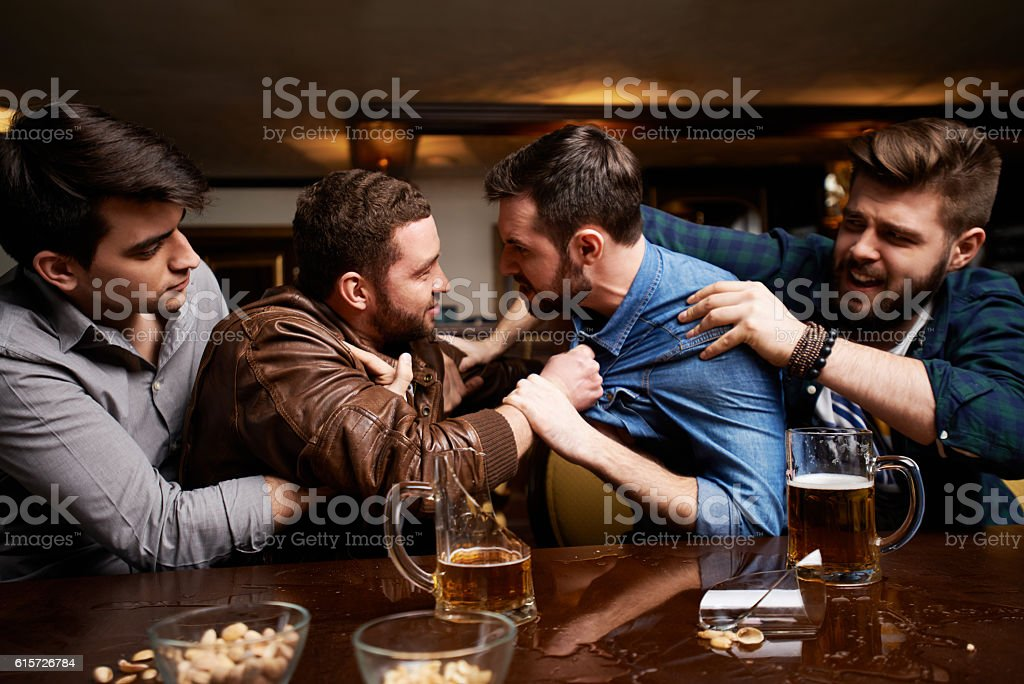 Drunk men fighting in pub, their friends trying to - foto de stock