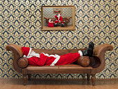 Drunk Santa Claus lying down on sofa and drinking wine