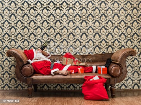 Drunk Santa Claus lying on sofa and drinking wine