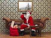 Drunk Santa Claus sitting on sofa and drinking wine