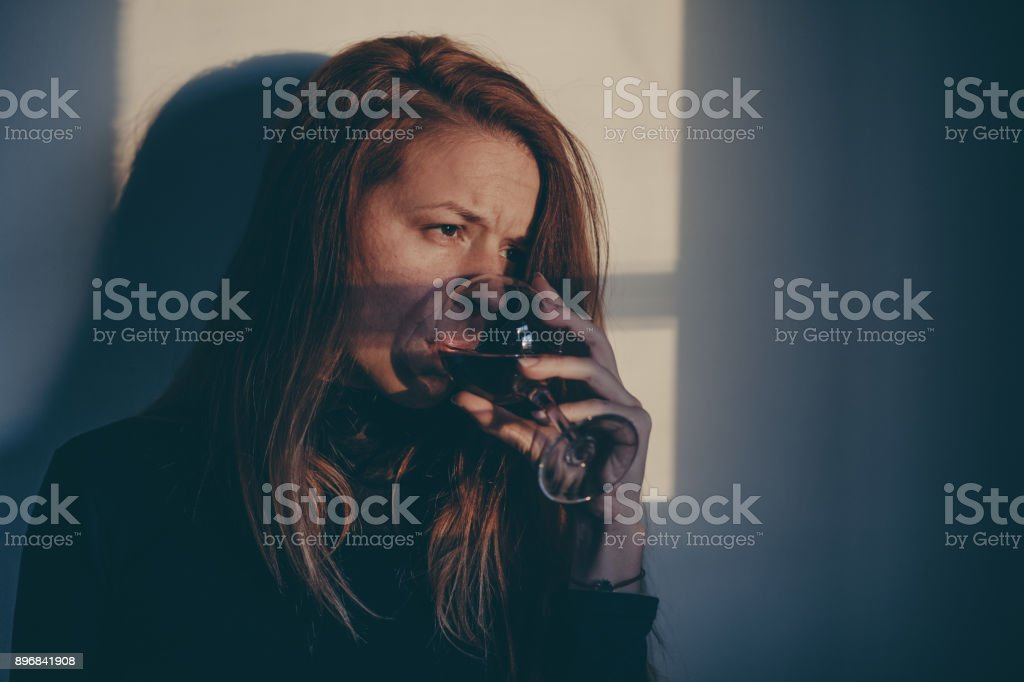 Drunk woman drinking wine alone and depressed stock photo