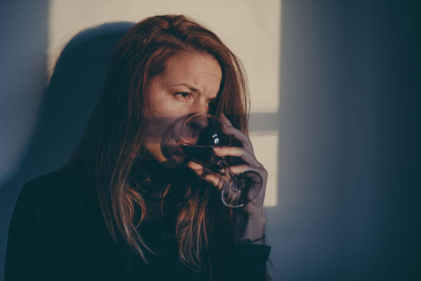 drunk woman drinking wine alone and depressed - dipsomania stock pictures, royalty-free photos & images