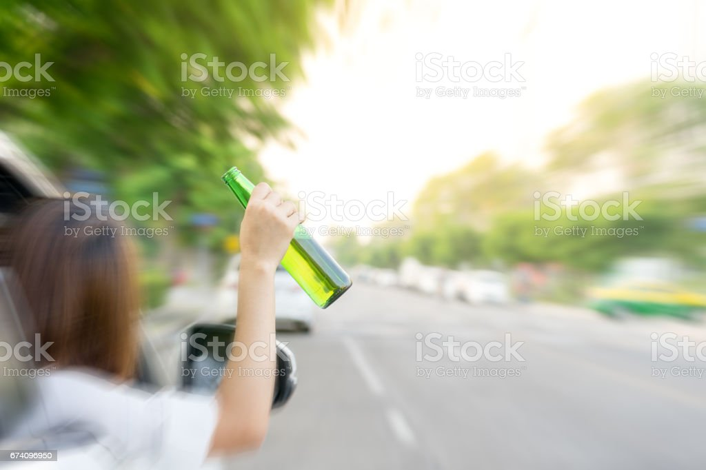Drunk woman driving and holding beer bottle outside a car. stock photo