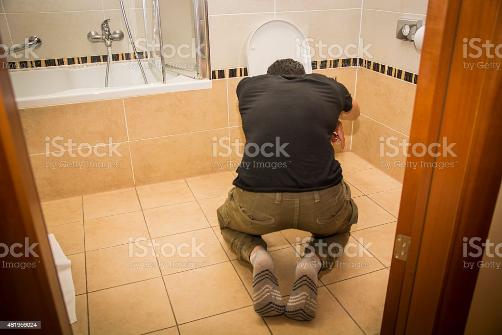 Drunk Young Man Vomiting in the Toilet at Home stock photo