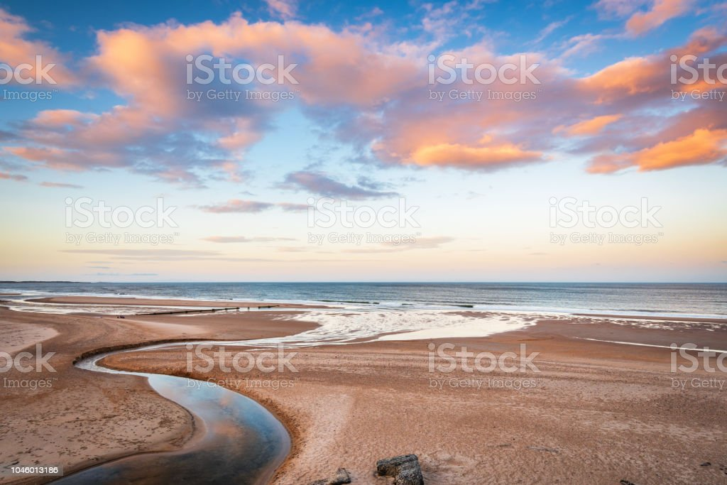 Druridge Bay and Dunbar Burn near sunset Druridge Bay is a seven mile long beach in Northumberland between Amble to the north and Cresswell to the south Bay of Water Stock Photo
