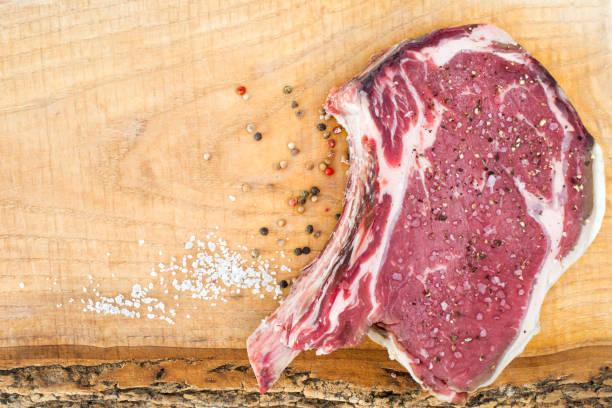 trocken im alter von 60 tagen - frenched alter beef rib steak auf eiche holzplatte mit salz und pfeffer - wie alt werden kühe stock-fotos und bilder