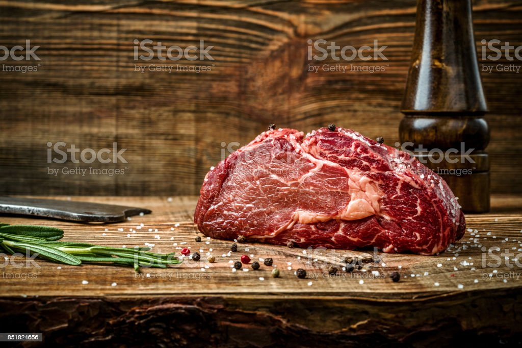 Dry aged Ribeye Steak with seasoning on wooden background stock photo
