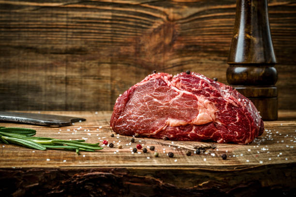 dry aged ribeye steak with seasoning on wooden background - beef stock pictures, royalty-free photos & images