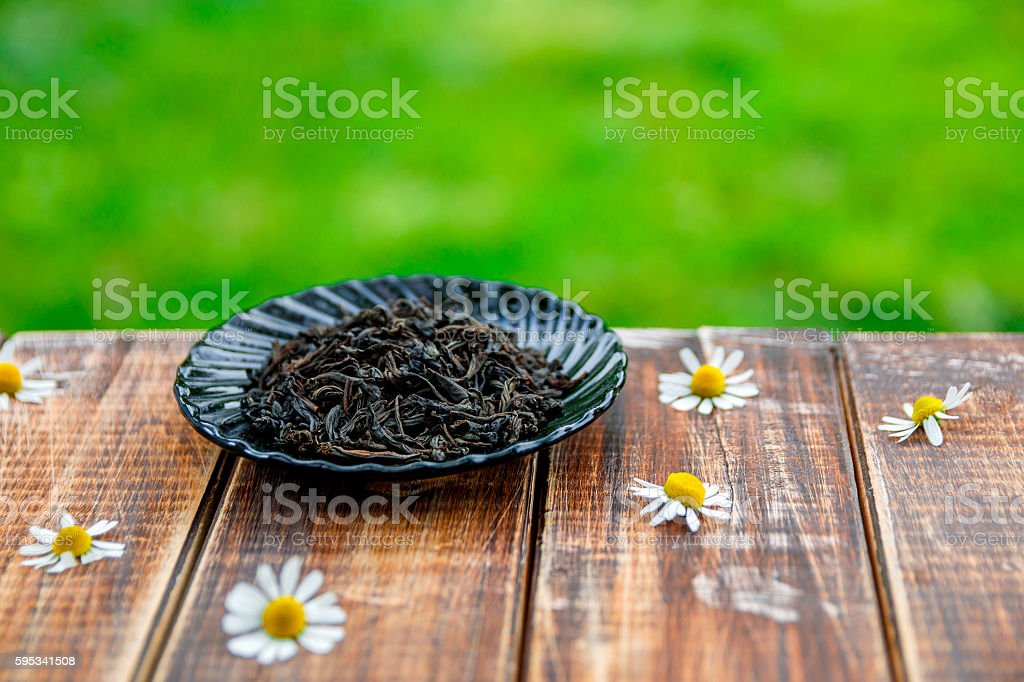 Dry Black tea on plate  wooden table with chamomile stock photo