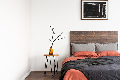 Dry branch in glass vase on wooden nightstand table nest to king size bed with orange and grey bedding
