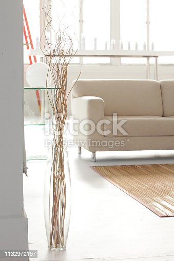 a tall glass glass vase and dry branches are decorated in setup of living room in white studio
