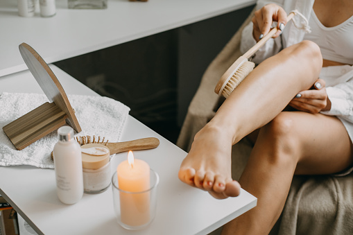 Dry brushing body brush for exfoliating dry skin, lymphatic drainage and cellulite treatment. Woman brushing skin leg with dry wooden brush to prevent cellulite and body problem in bedroom at home.