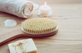 istock Dry brushing the skin in a pattern with a dry brush, usually before showering help reduce cellulite and remove toxins in human body. Selective focus on firm, natural bristle brush with a long handle. 1142844649