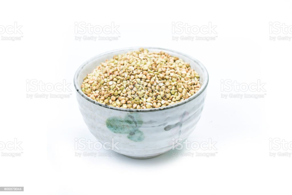 Dry buckwheat in white ceramic bowl isolated on white. Spilled buckwheat. stock photo