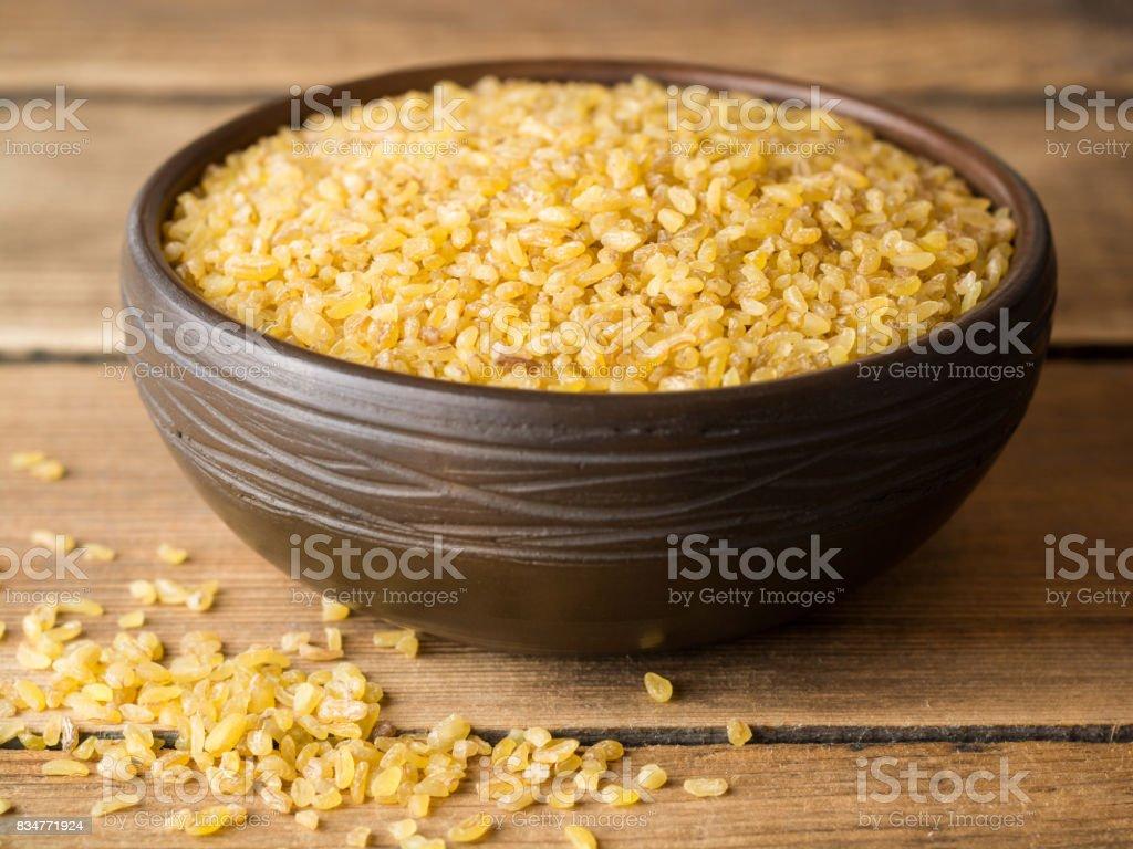 Sécher le boulgour dans un bol en céramique sur fond en bois rustique - Photo