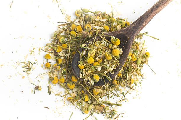dry camomile tea into a spoon - planta de manzanilla fotografías e imágenes de stock