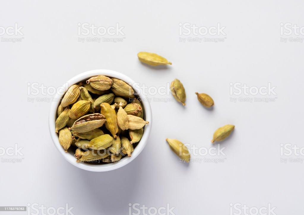 Dry cardamom pots in a white bowl Dry cardamom pots in a white bowl on a grey background, top view. Antioxidant Stock Photo