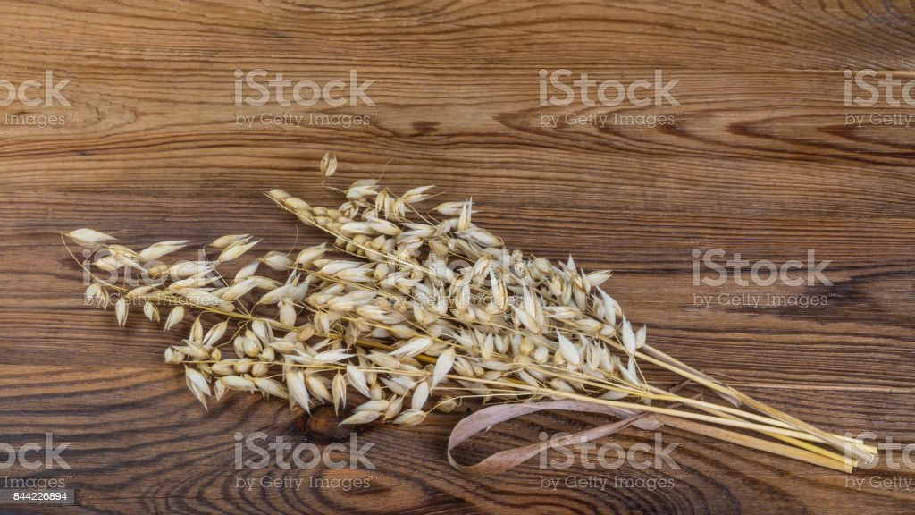 Dry cereal ears on a wooden table in HD ratio 16x9 stock photo