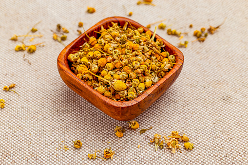 Dry chamomile herbs on linen background.  Healthy lifestyle