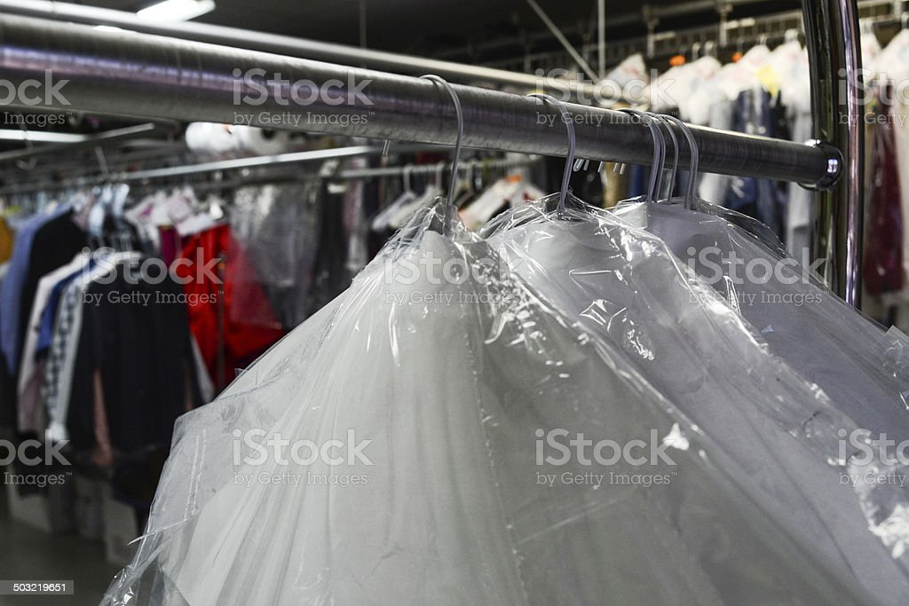 Dry cleaned clothes in plastic with business in back stock photo