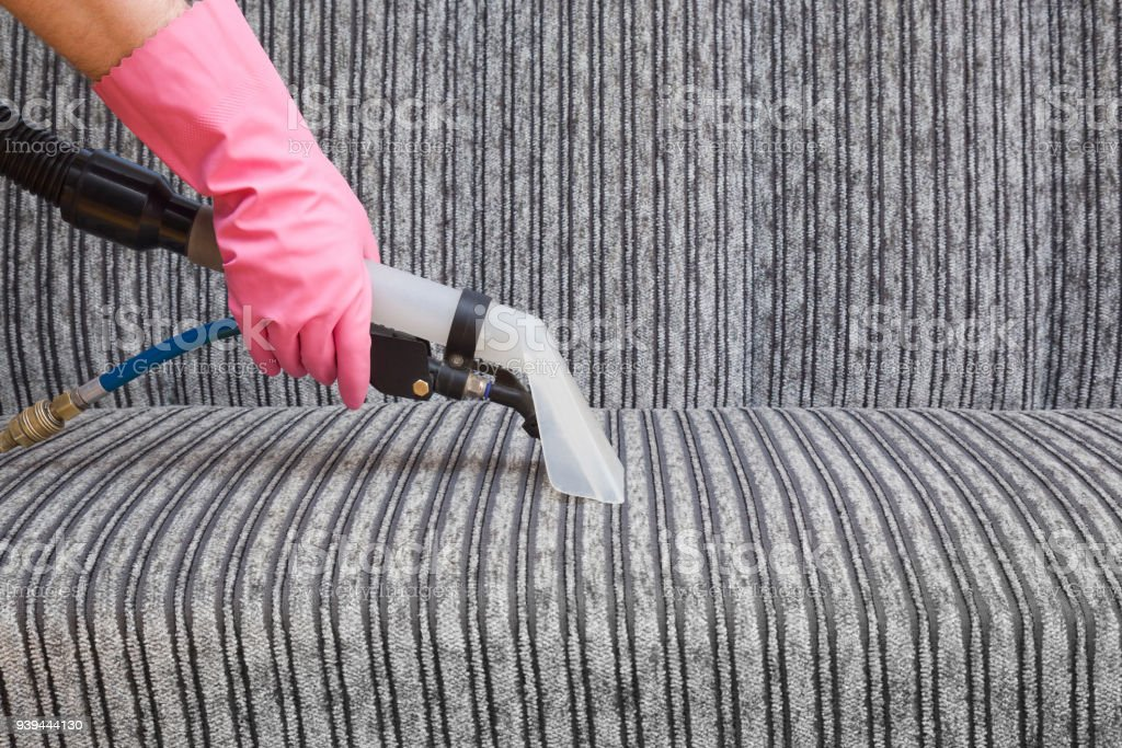 Dry cleaner\'s employee hand cleaning a modern sofa with...